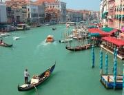 Barcos e gôndolas no Grande Canal, com prédios em contato direto com a água